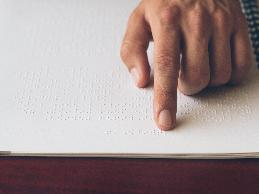 person reading a Braille document