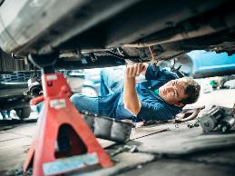 A mechanic with a bending restriction due to a low back impairment has problems accessing the engine compartment and low task areas of vehicles.